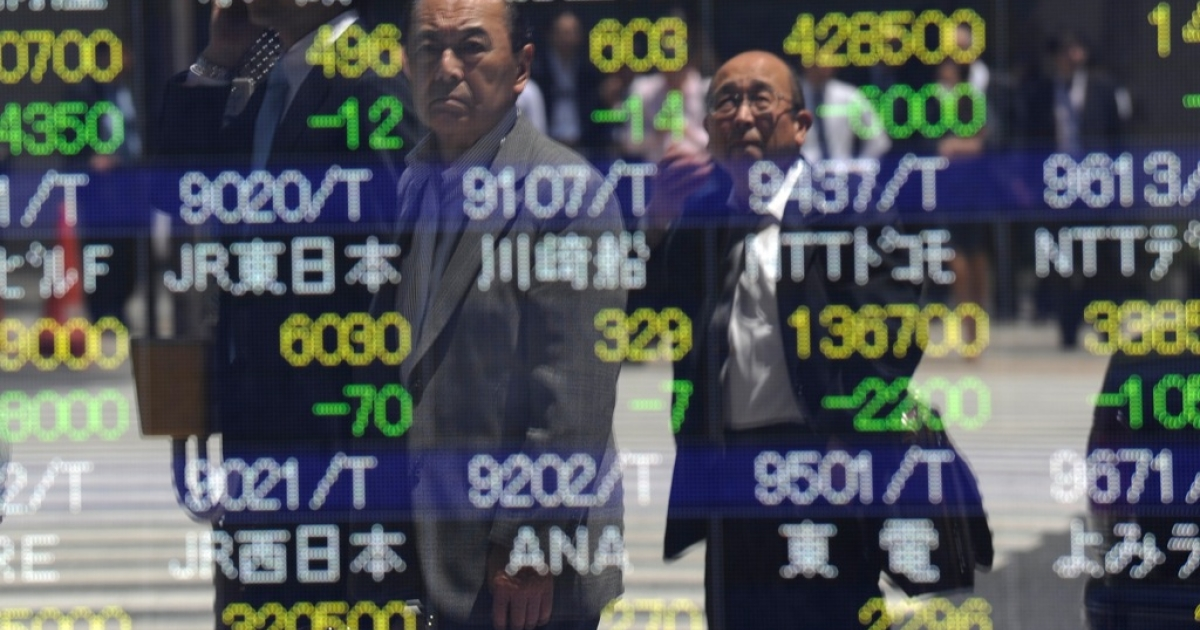 Men reflect on an electric quotation board flashing share prices of the Tokyo Stock Exchange (TSE) in front of a securities company in Tokyo on May 21, 2010.</p>