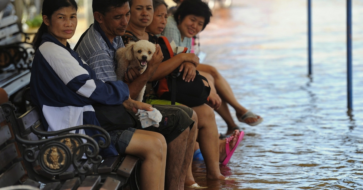 Bangkok residents sit on a bench in floodwater in the Thai capital on October 26, 2011.</p>