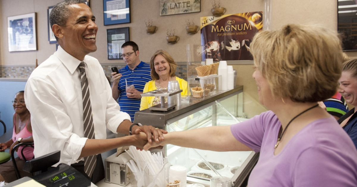 US President Barack Obama greets employees as he orders ice cream during a surprise stop at Deb's Ice Cream and Deli in Cedar Rapids, Iowa, on July 10, 2012.</p>