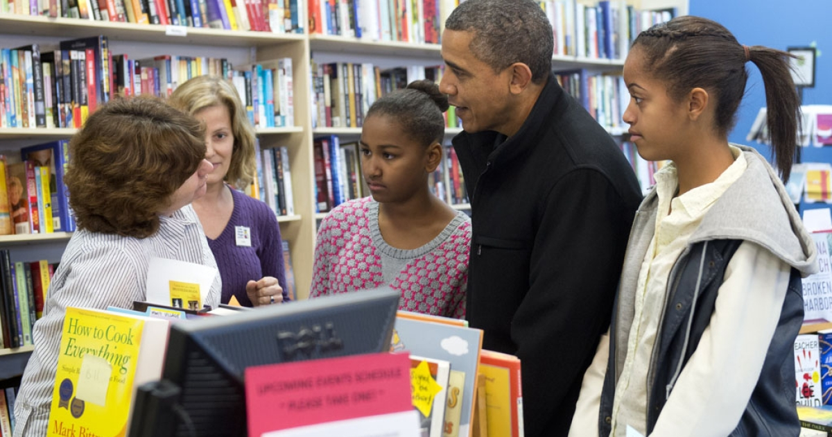 US President Barack Obama talks with a shopkeeper alongside his daughters Sasha and Malia (right) during a shopping trip to One More Page Books on Small Business Saturday in Arlington, Virginia, on November 24, 2012.</p>