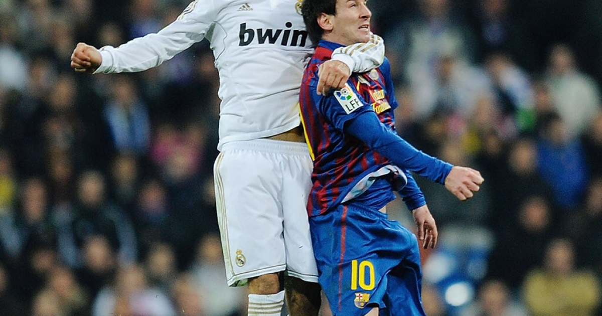 MADRID, SPAIN - JANUARY 18: Fernando Carvalho (L) of Real Madrid tackles Lionel Messi of Barcelona during the Copa del Rey Quarter Finals match between Real Madrid and Barcelona at Estadio Santiago Bernabeu on January 18, 2012 in Madrid, Spain.  (Photo by Denis Doyle/Getty Images)</p>