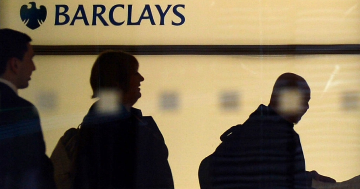 People walk past a Barclays logo at the bank's headquarters in Canary Wharf in east London.</p>