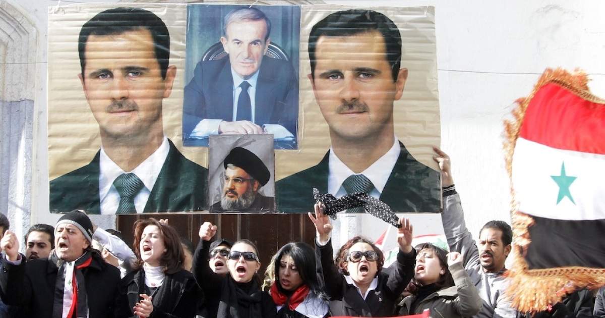 Syrian mourners shout slogans as they stand under pictures of Syrian President Bashar al-Assad (L and R), late president Hafez al-Assad (top C) and Lebanon's Hezbollah chief Hassan Nasrallah during the mass funeral of 44 people killed in twin suicide bombings which targeted intelligence agency compounds at the Omayyad Mosque in Damascus on December 24, 2011.</p>