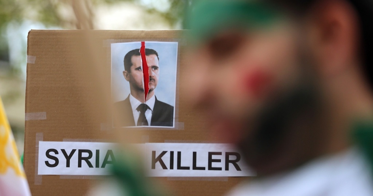 A sign denouncing Bashar al-Assad, President of Syria, is displayed at a rally of groups opposing Iranian President Ahmadinejad's speech at the United Nations General Assembly in September 2012.</p>