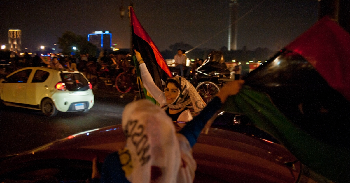 Two Cairo women wave Libyan flags from a moving car after the news of Muammar Gaddafi's death spread though the streets Oct. 20.</p>