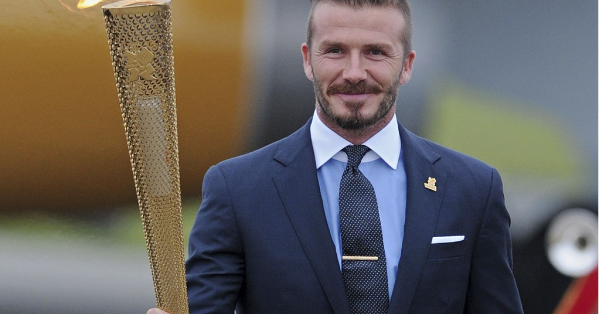 David Beckham carries the Olympic torch in Cornwall, England, on May 18, 2012. The torch relay starts Saturday at Land's End, the southwest tip of England, on an 8,000-mile journey around the UK to Olympic Stadium for the opening of the Games on July 27.</p>