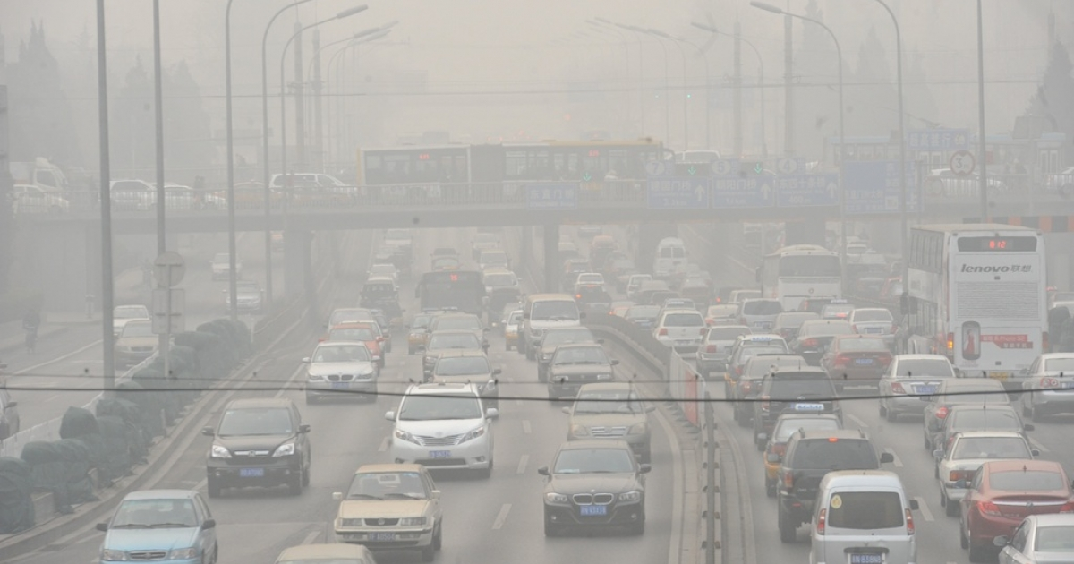 Vehicles make their way along a road on a smoggy day in Beijing. Beijing's government bowed to a vocal online campaign for a change in the way air quality is measured in the Chinese capital, one of the world's most polluted cities.</p>