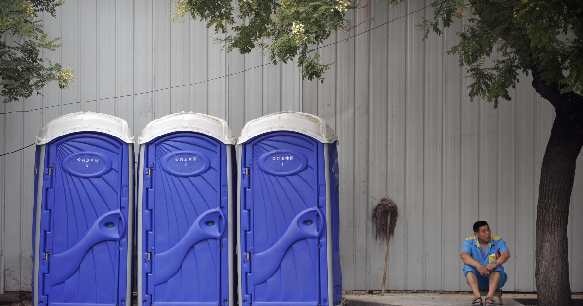 An attendent sits next to portable toilets in Beijing on July 23, 2008. The new cleanliness rules are similar to the ones put in place during the Olympic games.</p>