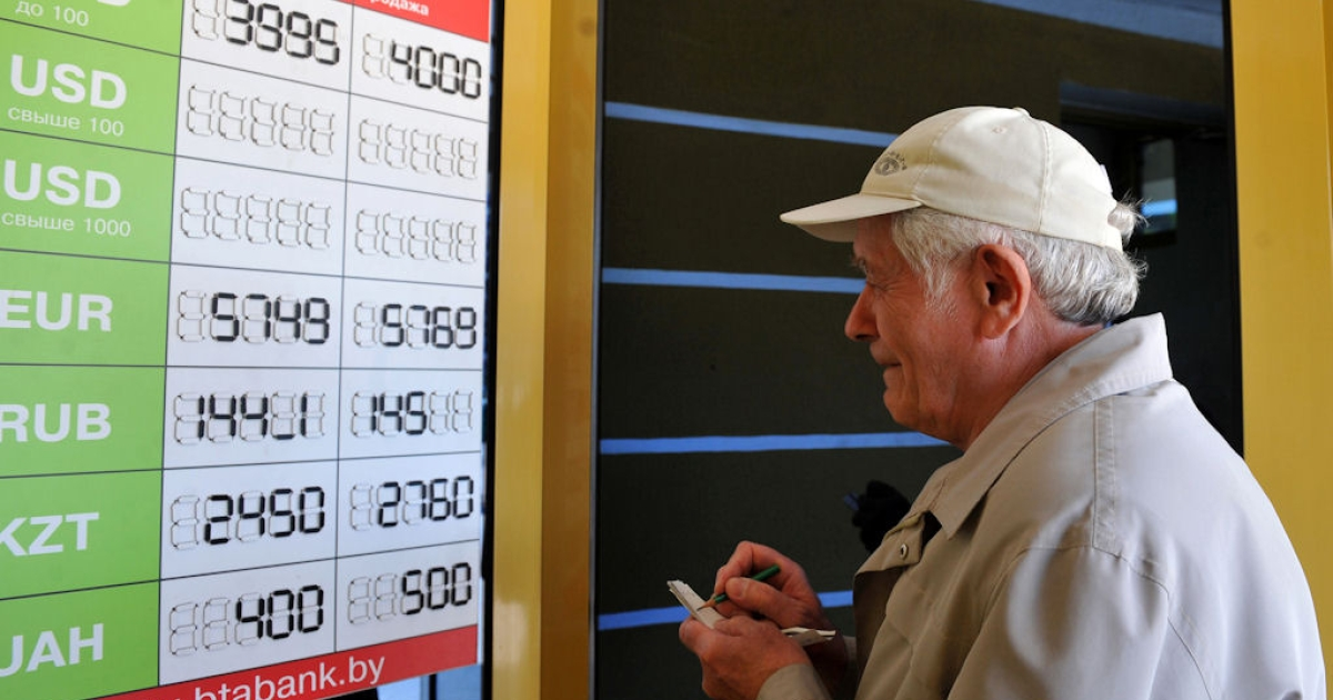 An elderly man takes notes while reading foreign currency rates against the Belarus ruble outside an exchange office in Minsk, on May 11, 2011.</p>