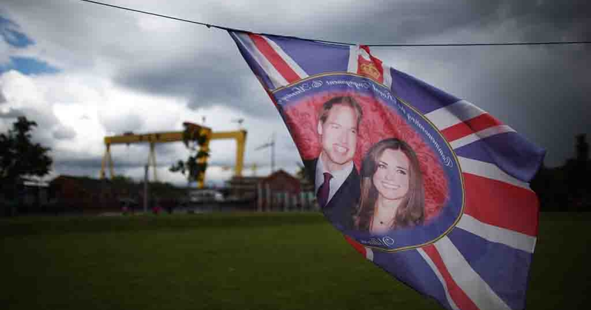 A flag with images of The Duke and Duchess of Cambridge flutters in East Belfast, Northern Ireland.</p>