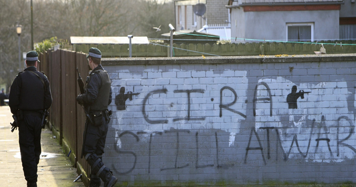 Armed policemen walk past a wall with the words 'CIRA Still At War' sprayed on it in a residential estate in Craigavon, Northern Ireland, on March 10, 2009. In nearby Belfast, a total of 62 police officers were injured in 24 hours in clashes between rival Protestant and Catholic gangs.</p>