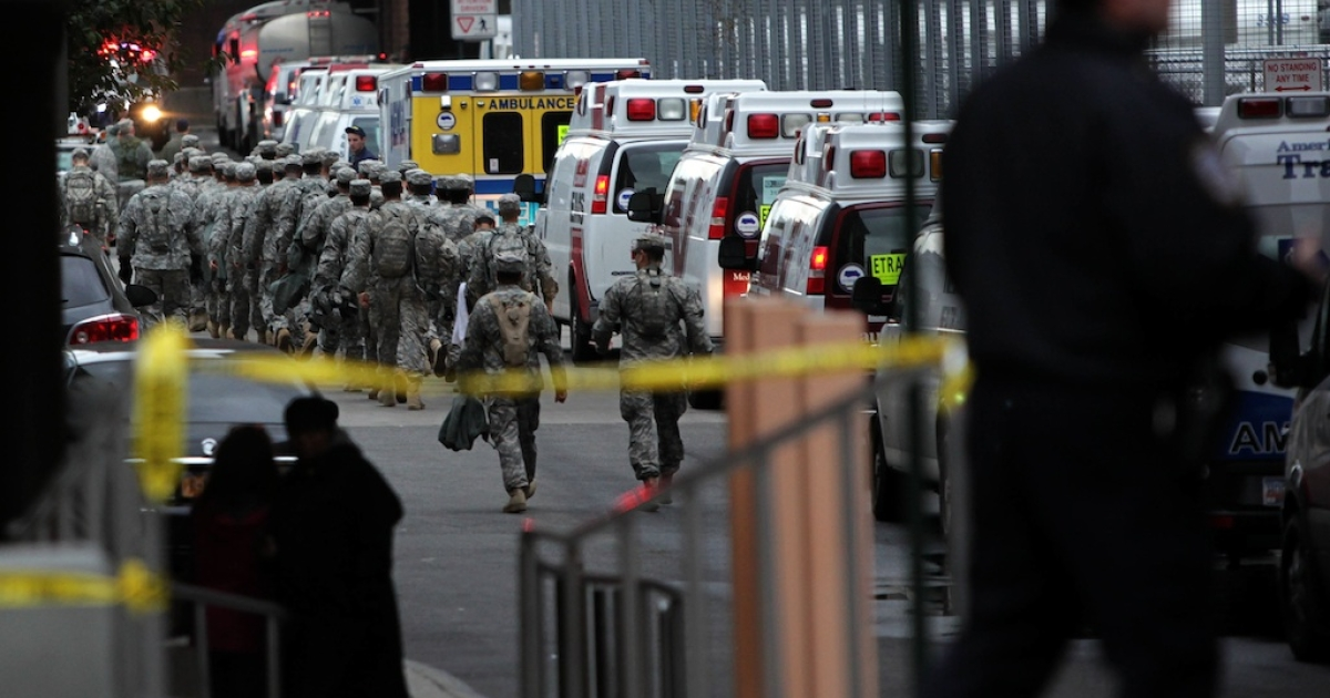Military personnel aid during an evacuation of Bellevue Hospital October 31, 2012 in New York City. The hospital had been operating on backup generators since losing power during Hurricane Sandy but had to be evacuated once the extent of the damage became clear.</p>