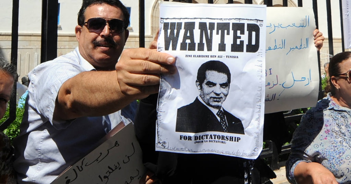 A man holds a wanted poster for deposed Tunisian Zine el Abidine Ben Ali outside of the courthouse. Ben Ali and his wife were found guilty of misusing public funds, and were sentenced to 35 years in prison each.</p>