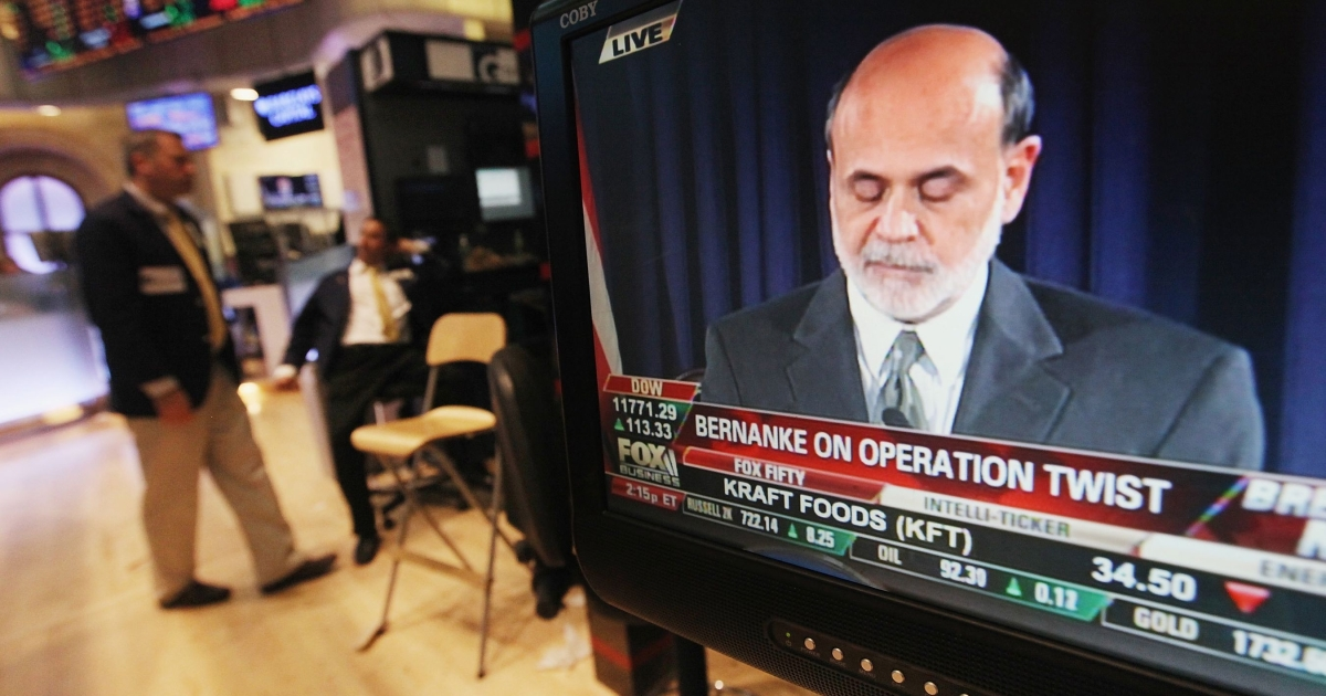 Wall Street traders gather near a TV playing Fed Chairman Ben Bernanke's news conference on November 2, 2011 in New York City.</p>