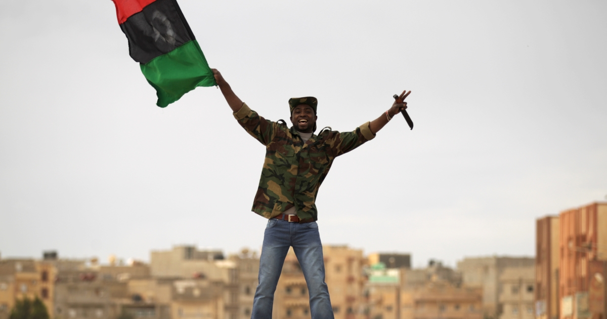 A Libyan rebel fighter holds a knife as he waves the revolution flag in a street of Benghazi on March 19, 2011.</p>