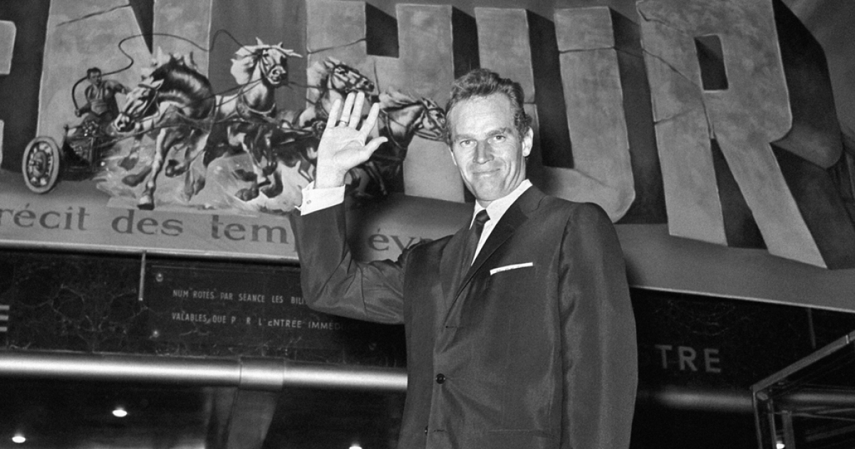 US actor Charlton Heston poses in front of the poster of his last film
