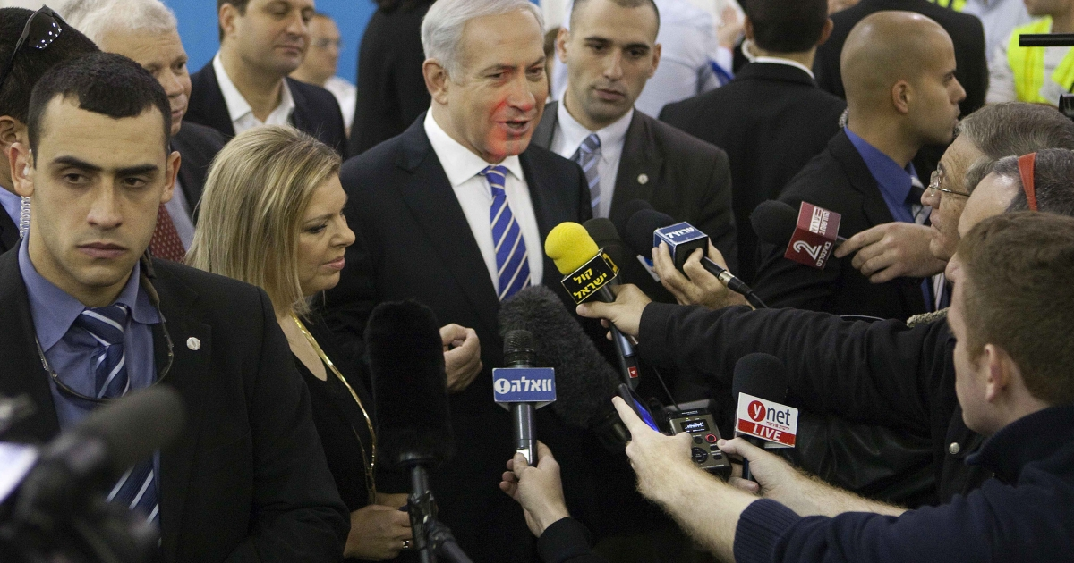 Israeli Prime Minister and Likud party leader Benjamin Netanyahu, accompanied by his wife Sara, speaks to the press after casting his ballot at a polling station for the party's primary vote last night in Jerusalem.</p>