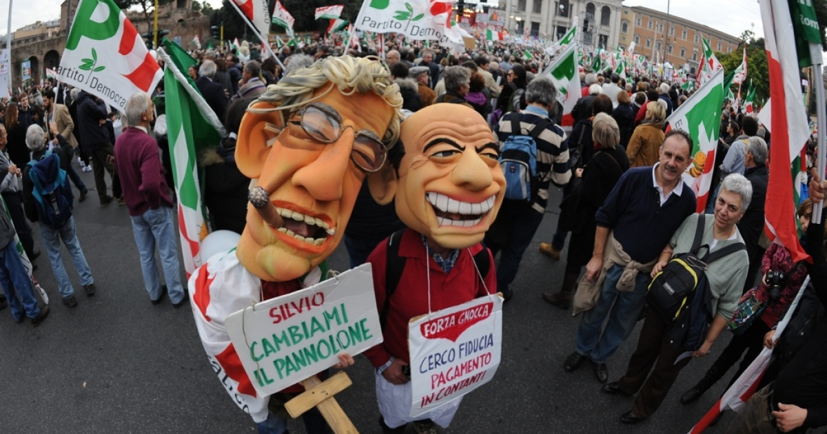 Demonstrators wearing masks of Italian Prime Minister Silvio Berlusconi (R) and the leader of the Northern League, Umberto Bossi, pose with placards reading 'Silvio, change the panorama' during a demonstration 'Reconstruction.'</p>