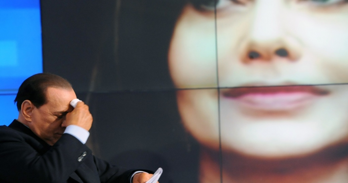 Italian Prime Minister Silvio Berlusconi is seen while a portrait of his wife, Veronica Lario, is projected in the background during the recording of 'Porta a Porta,' on an Italian channel on May 5, 2009, in Rome.</p>