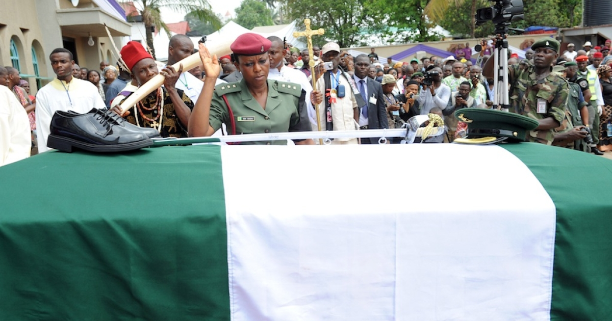 A soldier salutes after arranging the boots and cap on the casket of Nigeria's secessionist leader Odumegwu Ojukwu during his funeral at his native Nnewi country home in Anambra State eastern Nigeria, on March 2, 2012. Odumegwu Ojukwu, who championed the campaign for an independent Republic of Biafra in eastern Nigeria in the 1960s culminating in a 30-month civil war which left more than a million dead was buried at his Nnewi family home in Anambra State.</p>