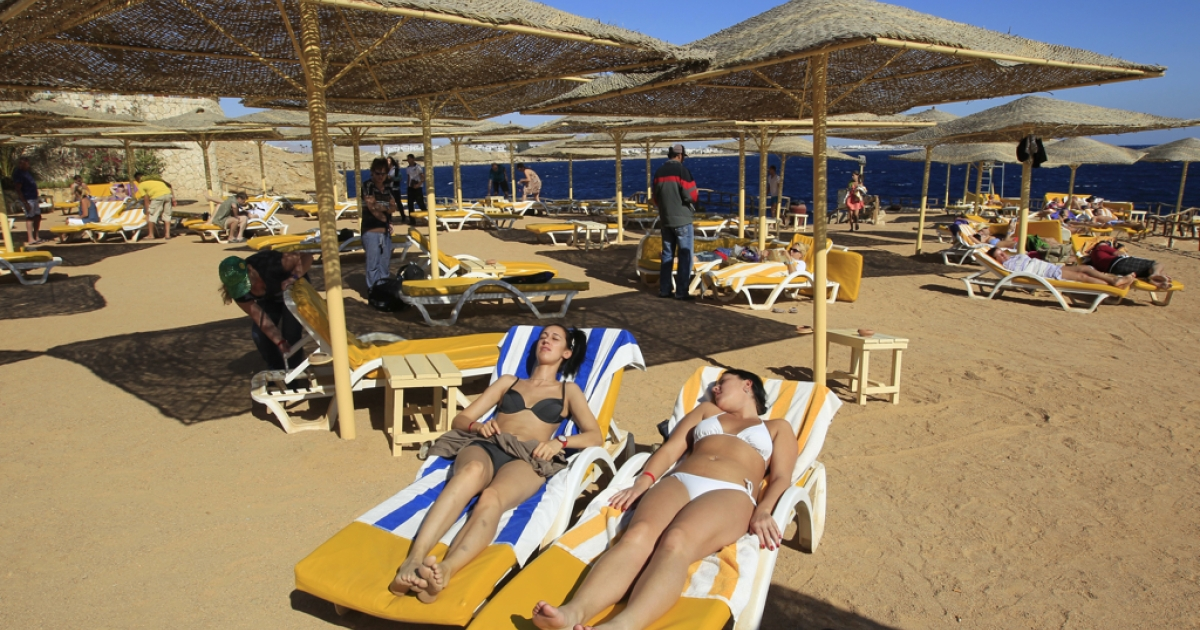 Bikini-clad tourists enjoy the beach in the Red Sea resort town of Sharm el-Sheikh,. With ultra-conservatives poised to play a big role in Egyptian parliament during an economic crisis, the Islamists' thoughts on what tourists may wear or drink are being scrutinised amid fears they will harm the country's vital tourism industry.</p>