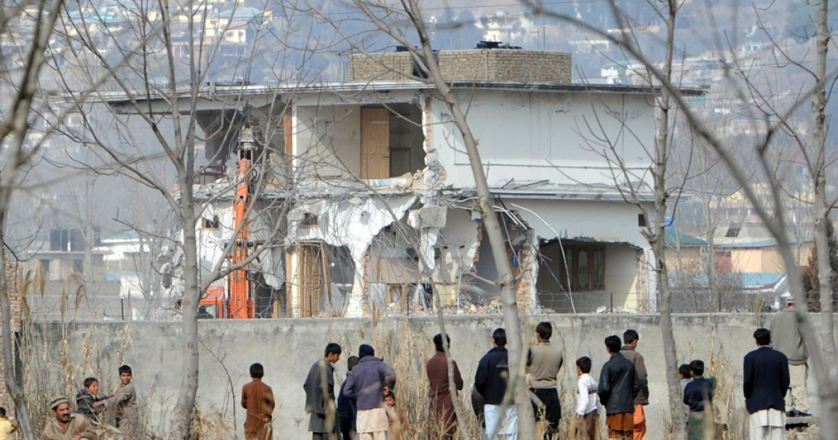 Local residents watch the demolition of the compound where Osama bin Laden was slain last year in the Pakistan town of Abbottabad on Feb. 26, 2012.</p>