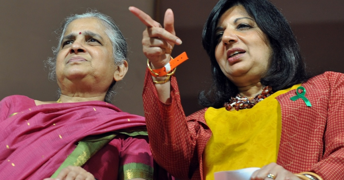 Entrepreneur and Biocon Chairman, Kiran Mazumdar Shaw (R) points towards a player while Sudha Murthy, (L), philanthrophist and wife of founder chairman of India's leading software company Infosys, N.R. Narayana Murthy, looks on during the IPL Twenty20 cricket match between Royal Challenger Bangalore and Rajasthan Royals at the M. Chinnaswamy Stadium in Bangalore on April 15, 2012.</p>