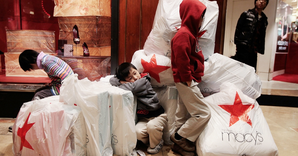 Children wait with shopping bags inside Macy's department store on