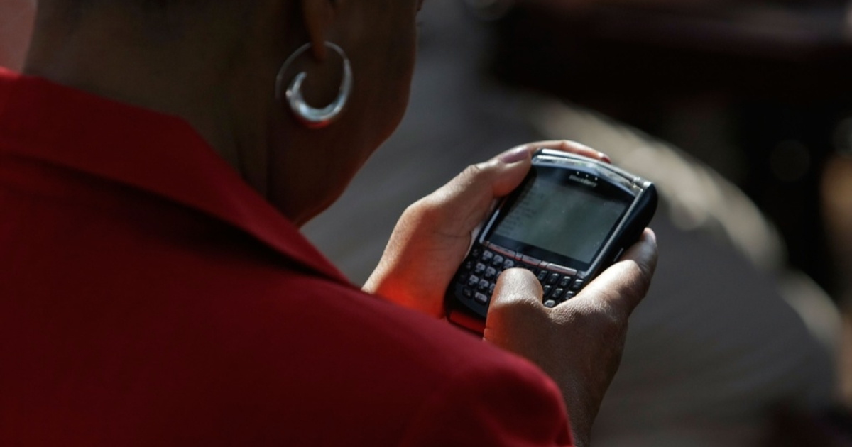 A woman works on her Blackberry phone.</p>