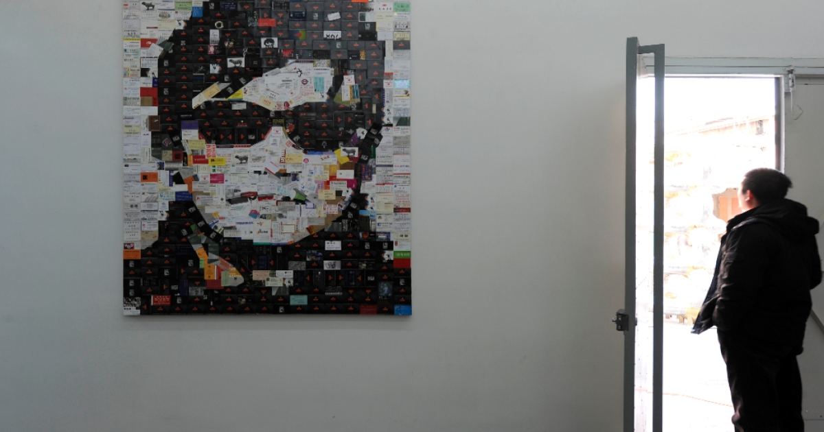 A visitor stands next to a piece of art work featuring blind human rights activist Chen Guangcheng on displayed at the 798 art district in Beijing on January 9, 2012.</p>