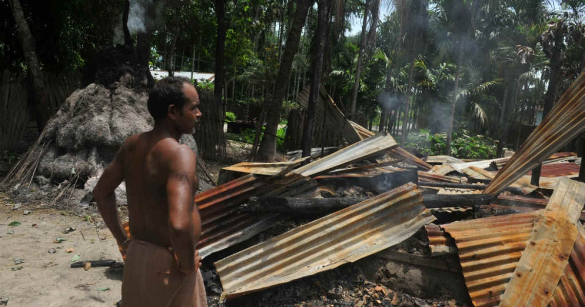 An Indian villager walks amidst the debris of his burnt house in the northeastern state of Assam.</p>