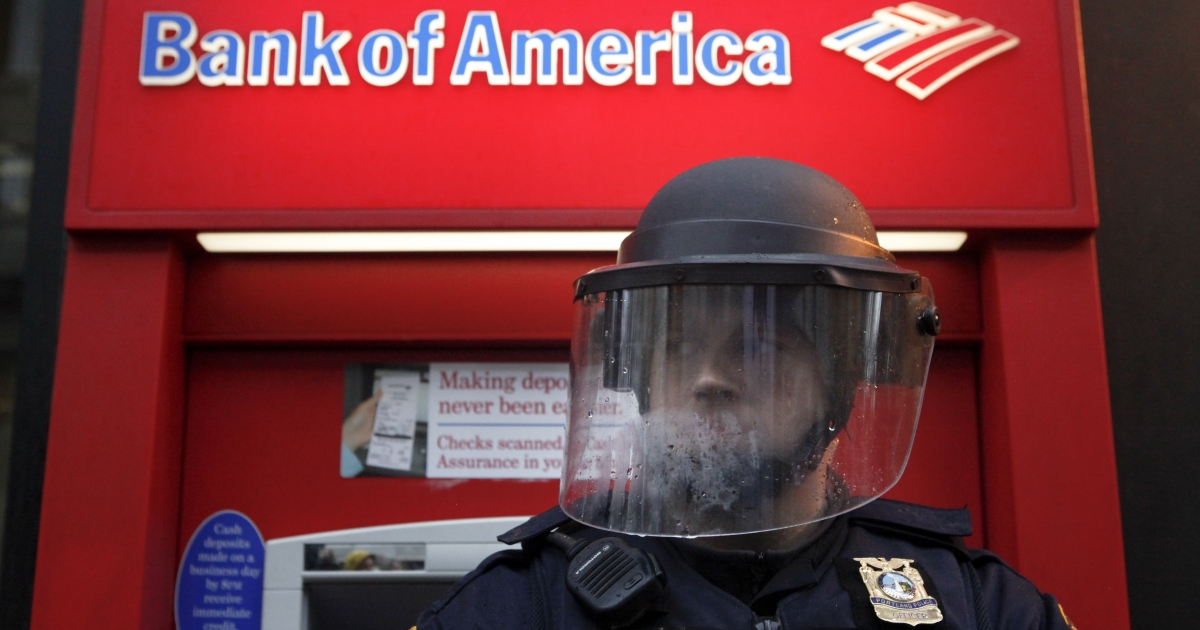 A policeman in riot gear defends a Bank of America as Occupy Portland protesters march past various banks in Portland, Ore., on Nov. 17, 2011.</p>