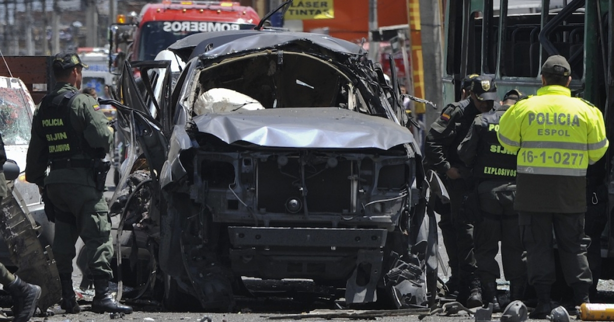Police officers inspect the wreckage of the car of former interior minister Fernando Londono on May 15, 2012 after an explosion ripped through a crowded area of Bogota's commercial district.</p>