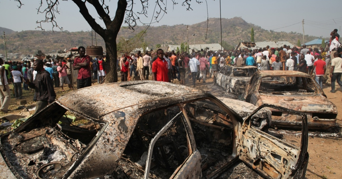 People gather around burnt cars after a bomb blast in Abuja.</p>