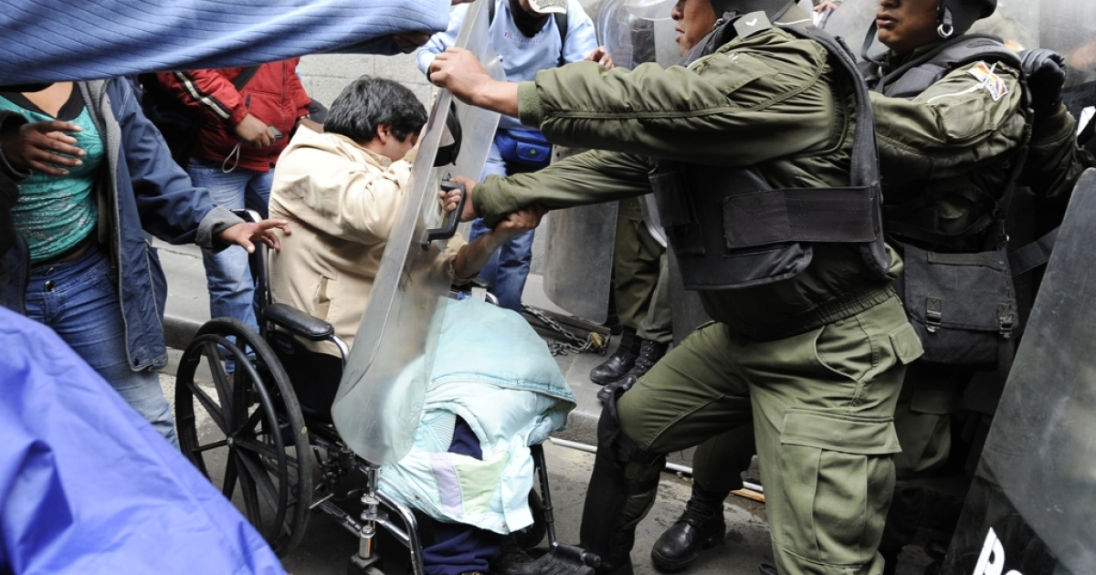Protesters in wheelchairs and on crutches fought with riot police as they tried to get to the Plaza de Armas the Bolivian capital of La Paz on Feb. 23. The protesters were ending a 100-day, 1,000-mile march through Bolivia to demand a raise in disability welfare aid from the government of President Evo Morales.</p>