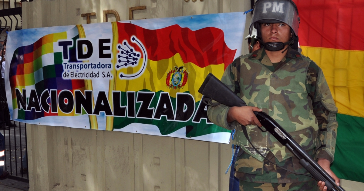 A Bolivian soldier stands guard at the entrance of the headquarters of the Spanish-owned electricity company Transportadora de Electricidad (TDE) next to a sign reading