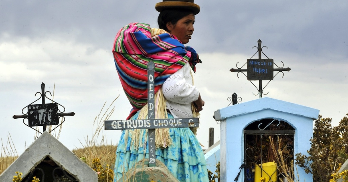 An Aymara woman walks in the Villa Ingenio cemetery in El Alto, 25 km west of La Paz, on November 2, 2011, during the religious festivity of the Day of the Dead, also known as All Souls Day in Bolivia.</p>