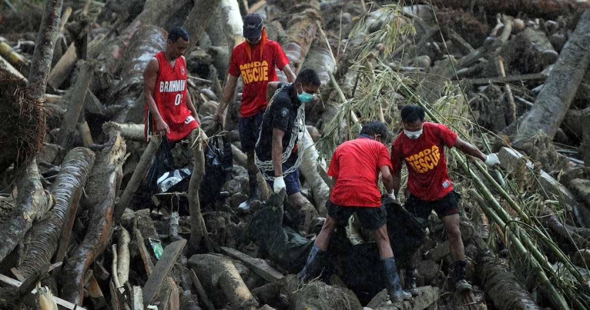 Rescue workers carry dead bodies, victims of flash floods at the height Typhoon Bopha and retrieved from amongst the debris of logs in New Bataan, Compostela Valley province on December 7, 2012. President Benigno Aquino vowed action on the Philippines' typhoon disasters December 7 as bruised and grieving survivors tried to recover from the latest that left nearly 500 people dead.</p>