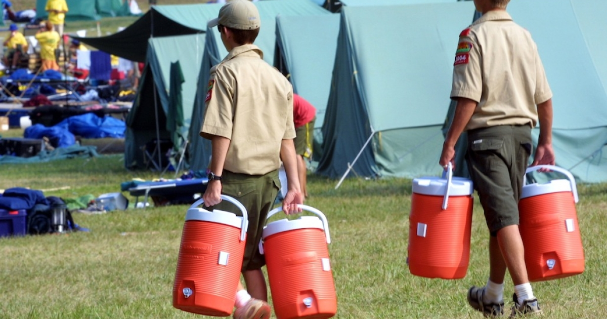 Two boy scouts carry water containers at the 15th National Scout Jamboree held at Fort A.P. Hill, VA, in 2001.</p>
