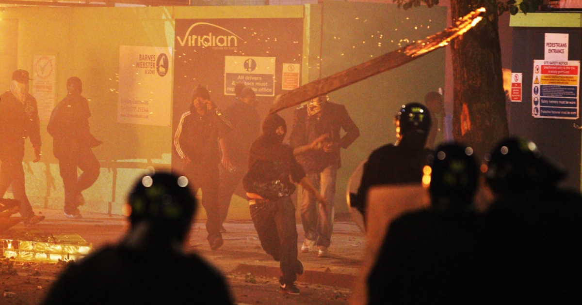 A rioter throws a burning wooden plank at police in Tottenham Aug. 7, 2011.</p>