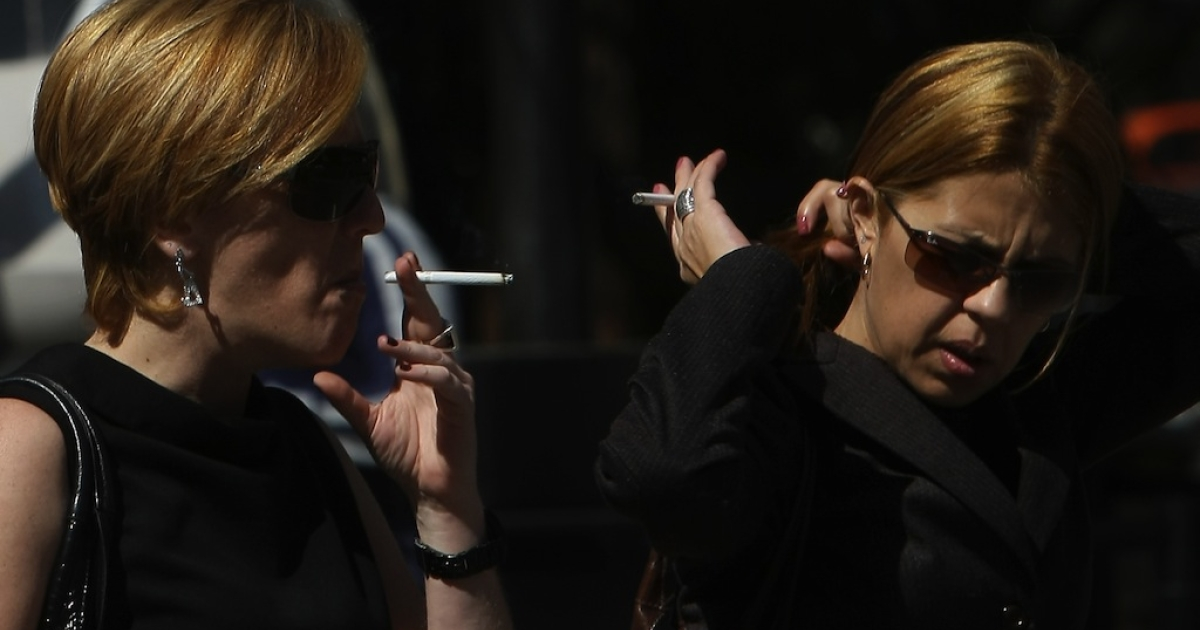 Two women smoke as they wait to cross an avenue in São Paulo, Brazil, on August 6, 2009.</p>