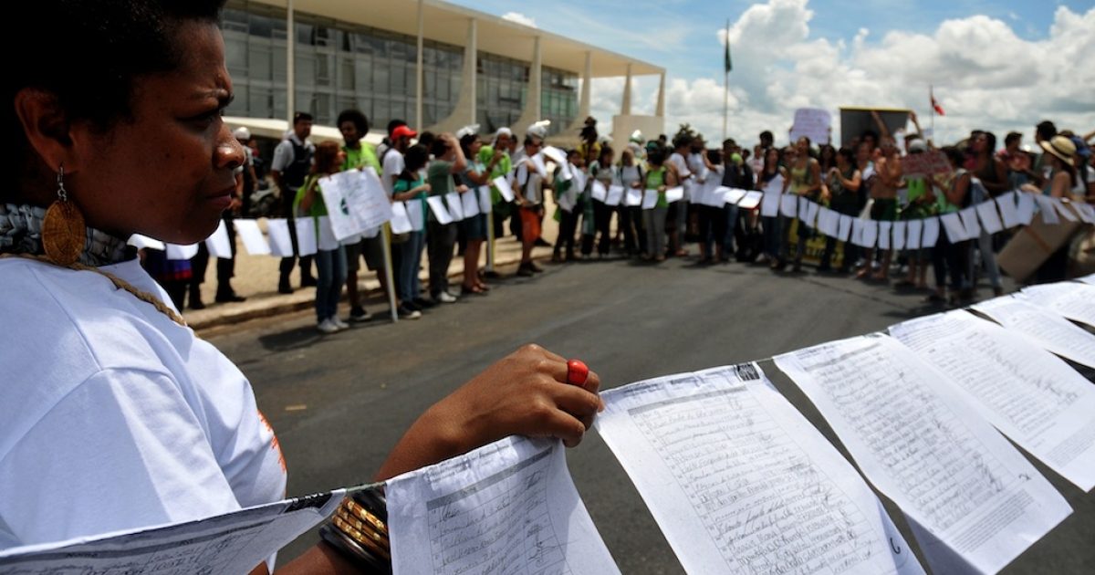 Environmental activists stand behind lists with signatures of more than one million people against the new Brazilian forest code, during a demonstration in front of the Planalto Palace, in Brasilia, on November 29, 2011.</p>