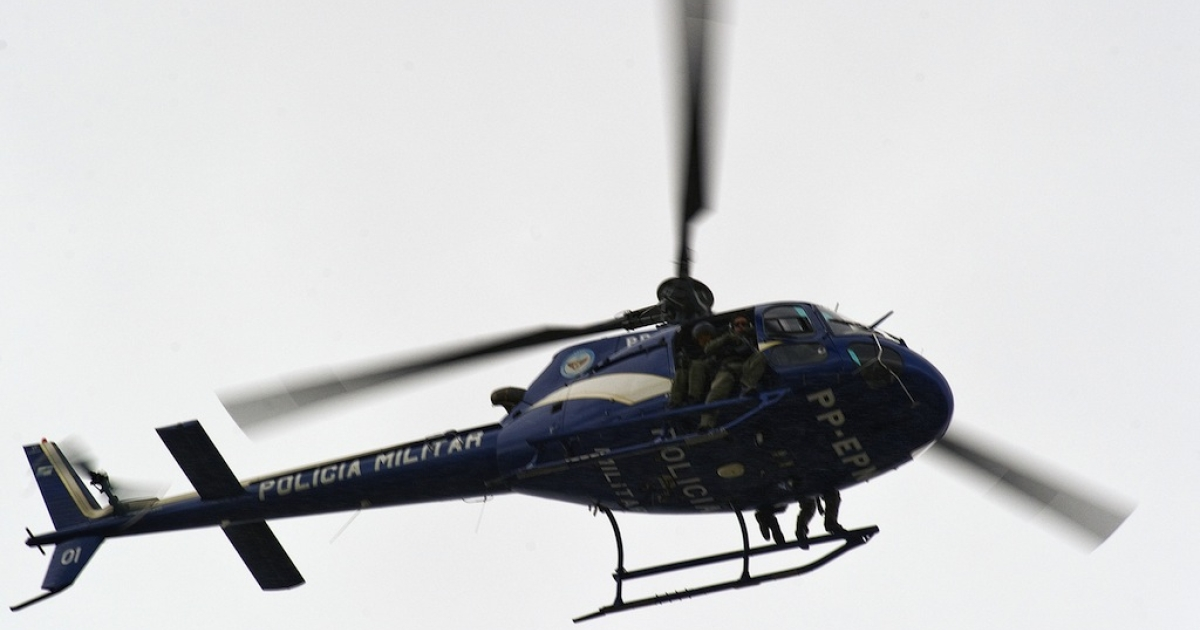 A Brazilian military police helicopter flies over Rio de Janeiro on November 24, 2010.</p>