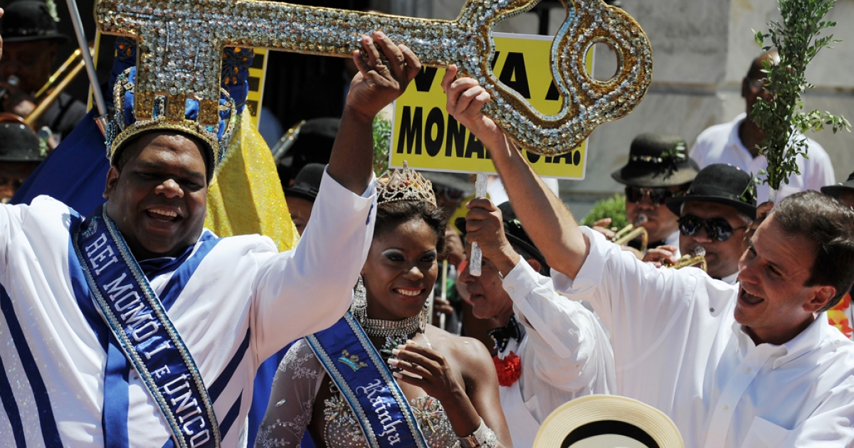 Carnival King Momo (L) gets from Rio's mayor Eduardo Paes (R) the keys to the city during the official launching of the 2012 Carnival in Rio de Janeiro, Brazil, on February 17, 2012. AFP PHOTO/VANDERLEI ALMEIDA (Photo credit should read VANDERLEI ALMEIDA/AFP/Getty Images)</p>