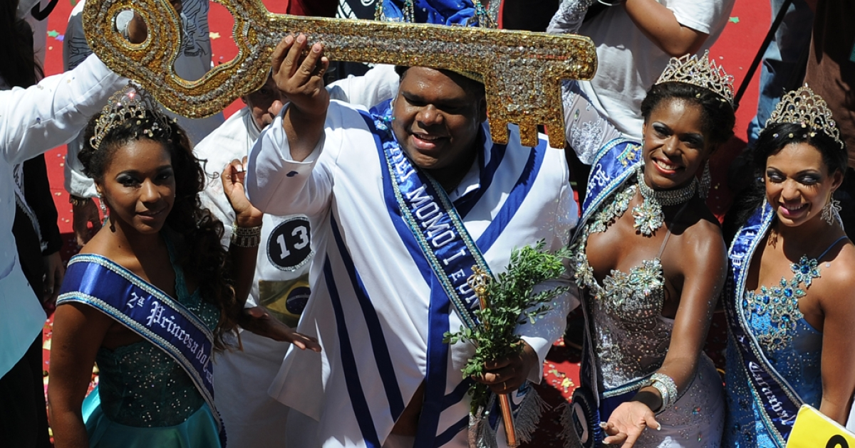 Carnival King Momo (C) shows the keys to the city he was given by Rio's mayor Eduardo Paes (not shown) during the official launching of the 2012 Carnival in Rio de Janeiro, Brazil, on February 17, 2012. AFP PHOTO/VANDERLEI ALMEIDA (Photo credit should read VANDERLEI ALMEIDA/AFP/Getty Images)</p>