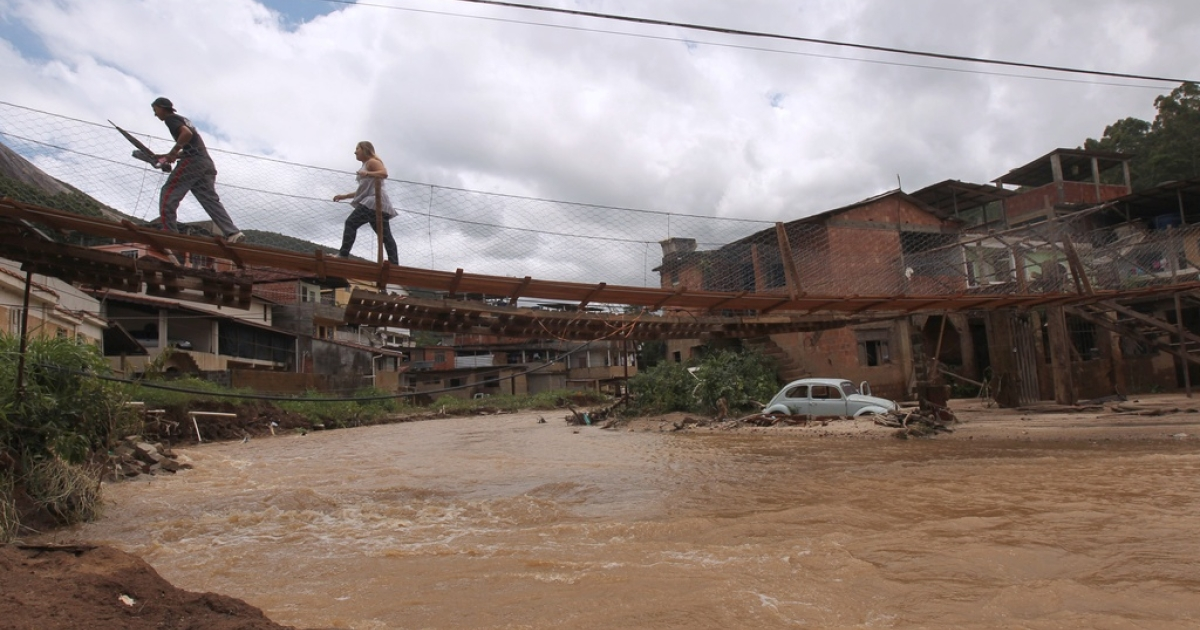 Here, in 2011, local residents cross a flooded road over a makeshift bridge 150 km north of Rio de Janeiro, Brazil. Floods and mudslides caused by heavy downpours in southeastern Brazil have now killed at least 20 people and forced another 40,000 to evacuate.</p>