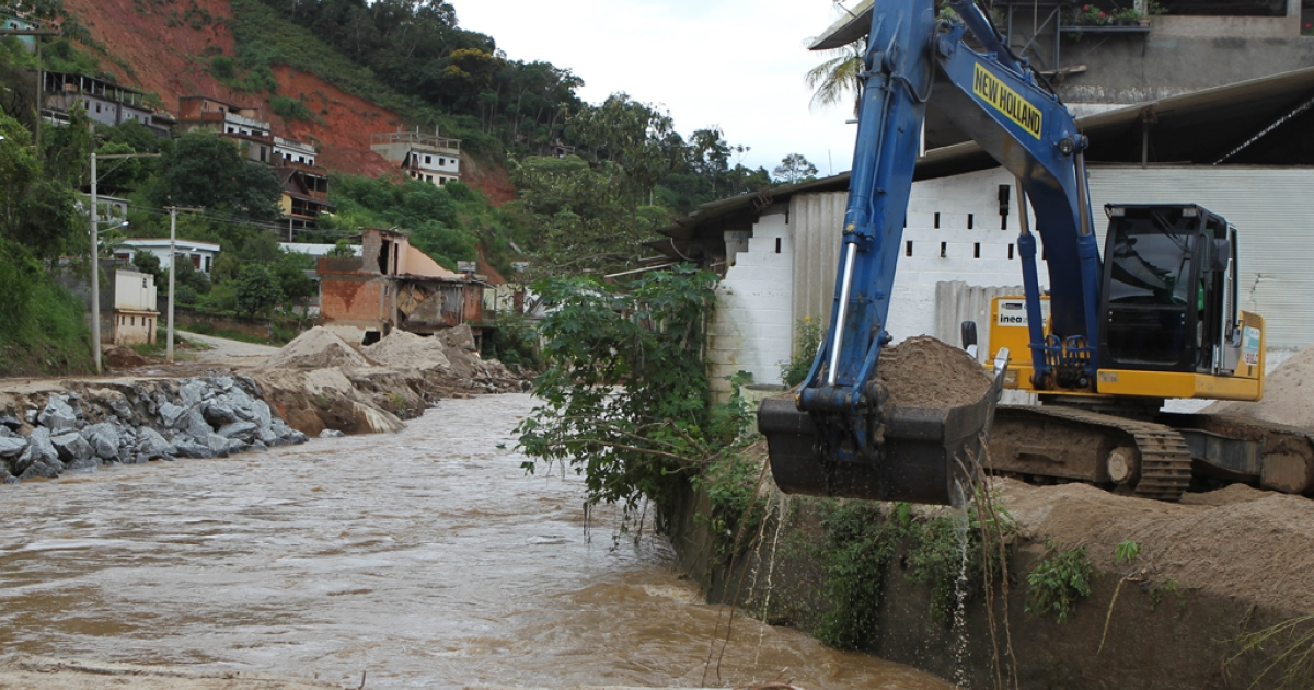 An excavator works trying to contain the water in a flooded road at the Corrego Dantas neighborhood in Friburgo, 150 km north of Rio de janeiro, Brazil on January 3, 2011. Six people dead, another one missing and 52 municipalities declared in a state of alert is the toll left by the summer rains season in southeastern Brazil so far.  AFP PHOTO/DANIEL MAGALHAES</p>