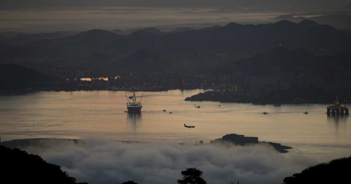 An airliner making its final approach (C) and oil rigs can be seen in this panorama of the Guanabara Bay at daybreak in Rio de Janeiro, Brazil, on May 24, 2012.</p>