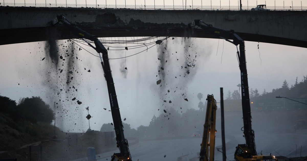 Workers demolish the south side of Mulholland overpass on the 405 freeway during the 53-hour total freeway closure resulting in massive traffic disruptions expected throughout the region on July 16, 2011 in Los Angeles, California.</p>
