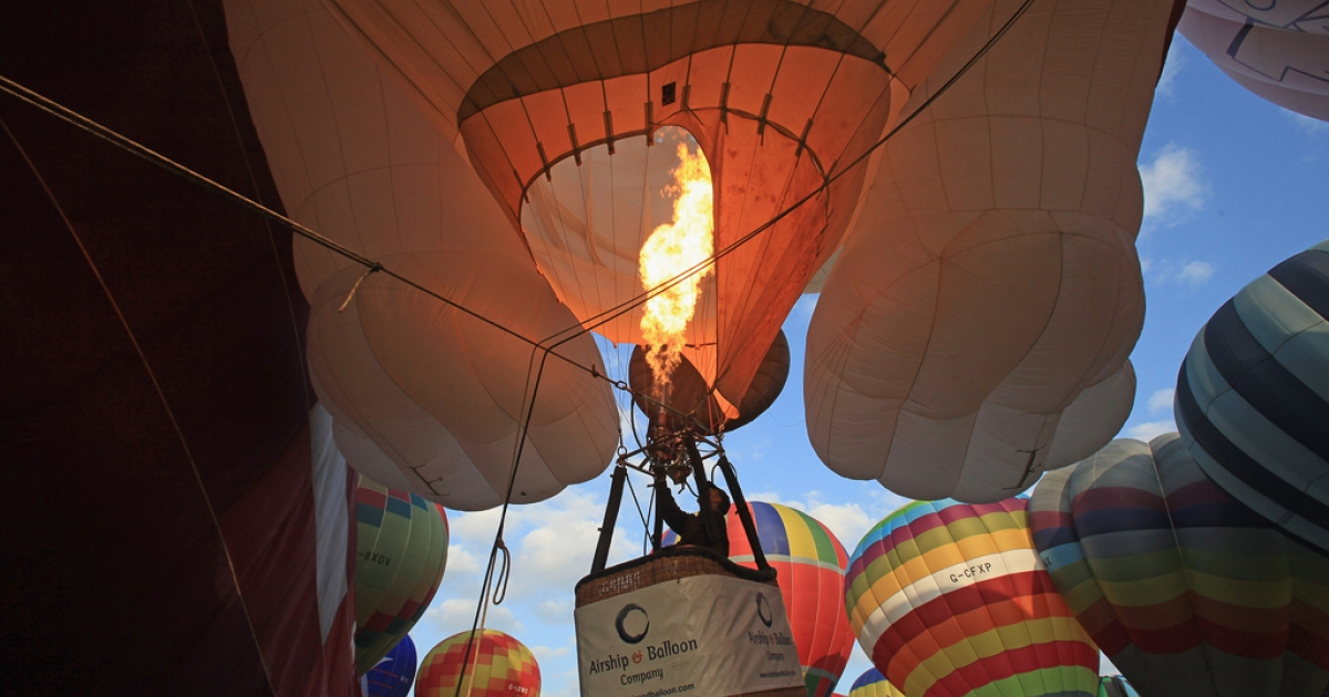 A balloonist fires his burners as he prepares to take-off at the dawn mass ascent at the 31st Bristol International Balloon Fiesta on August 7, 2009 in Bristol, England. Perfect flying conditions allowed over 100 balloons, of all shapes and sizes, to fly this morning at what has become Europe's largest hot air balloon festival.</p>